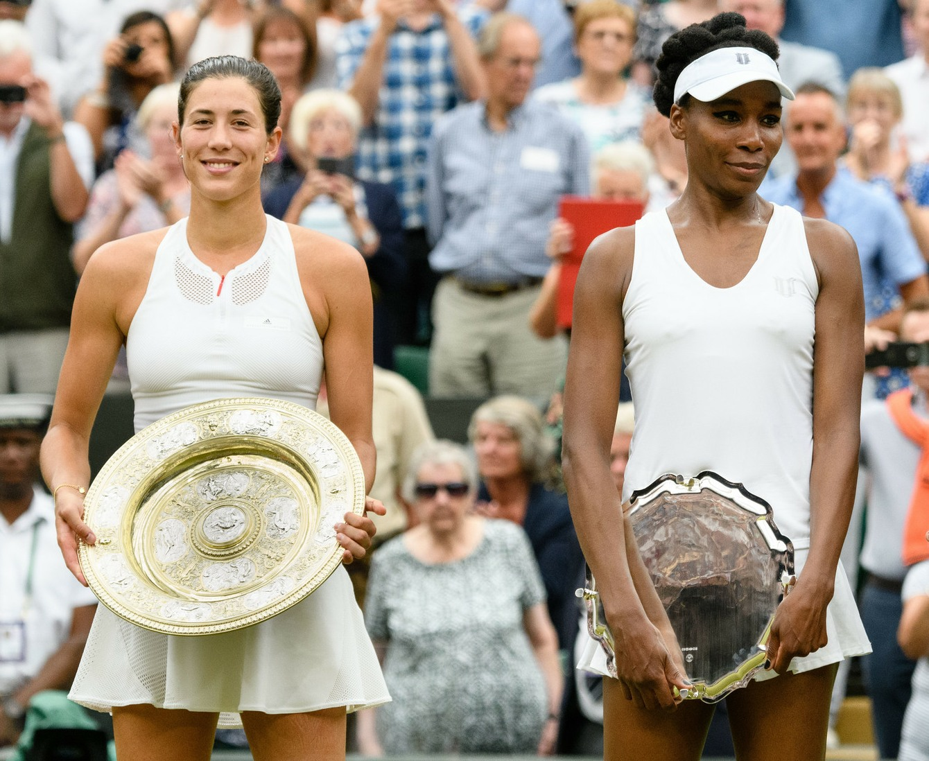 First time Wimbledon champion Garbine Muguruza holding next to Venus Williams with the runners up plate after winning in Straight sets during the Women's final match between Garbine Muguruza and Venus Williams on Centre Court on day twelve of the Wimbledon Lawn Tennis Championships