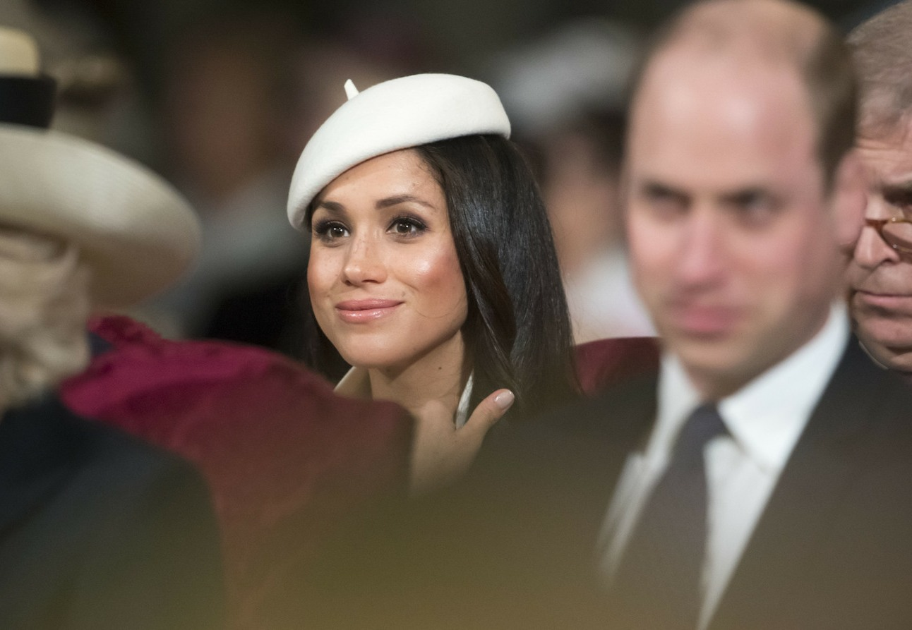 Meghan Markle, wearing a white Stephen Jones beret and a matching Amanda Wakeley crombie coat, attends the Commonwealth Day service at Westminster Abbey with her fiance Prince Harry