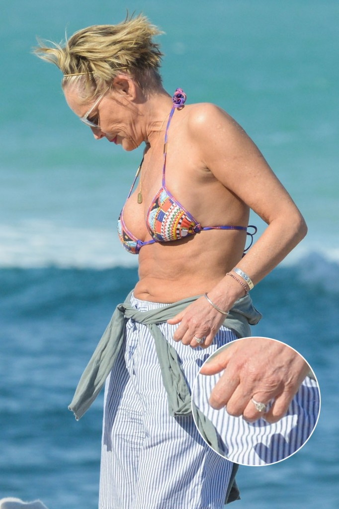 Sharon Stone flashes diamond ring on her left hand as she packs on PDA